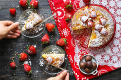 Lemon cake with strawberries, sugar end chocolate. Over an old wooden table with decorative napkins Stock Image