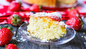 Lemon cake with strawberries, sugar end chocolate. Over an old wooden table with decorative napkins Stock Photo