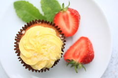 A lemon cake on white plate with strawberries, close up Stock Images