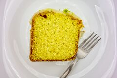 Free Lemon Cake With Icing. Detail Of Slice Of Lemon Cake With Icing And Lemon Zest On Plate With Fork In Top View. Royalty Free Stock Images - 200402139