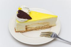 Lemon cheese cake with chocolate heart on a white plate Royalty Free Stock Photos
