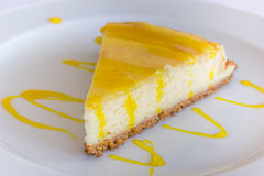 Lemon cheese cake with sauce on a white plate Stock Images