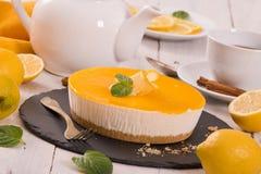 Lemon cheesecake. Lemon cheesecake with mint on black dish royalty free stock images