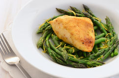 Lemon chicken with asparagus. Fresh, light and healthy dinner of skinless chicken breast and tender young asparagus spears with a lemon garnish Stock Photo