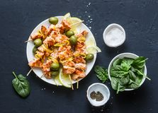 Lemon chicken skewers with olives and spinach on a dark background, top view. Flat lay stock image
