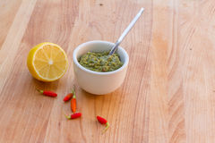 Lemon, chilli pepper and source on wooden cutting board, cooking Stock Photos