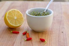 Lemon, chilli pepper and source on wooden cutting board, cooking Royalty Free Stock Image