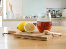 Lemon on chopping board and Glass of honey. Honey lemon - lemon on chopping board and Glass of honey and honey dipper on wooden table royalty free stock photos