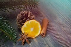 Lemon, cinnamon and badian next to pine branch. Piece of lemon, cinnamon and badian star anise next to pine branch and conifer cone, sitting on wooden table stock photography