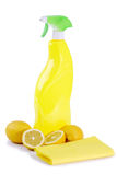 Lemon cleaner. A yellow bottle of household cleaner spray with fresh lemons on bright background royalty free stock photo
