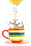Lemon, color cup and splash of tea Royalty Free Stock Photo