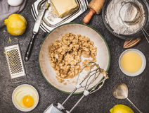 Lemon cookie or cake preparation with cooking ingredients. Butter and sugar mixing with hand mixer on dark kitchen table backgroun Royalty Free Stock Images