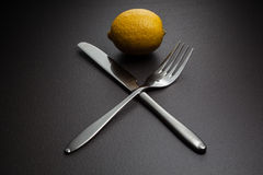 Lemon with crossed knife and fork on black Royalty Free Stock Photo