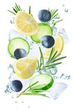 Lemon, cucumber, blueberry and rosemary flying with ices and water splash isolated royalty free stock photos