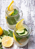Lemon and cucumber detox water in glass jars Royalty Free Stock Images