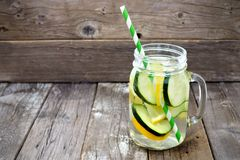 Lemon cucumber detox water in a mason jar against wood Stock Photos