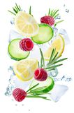 Lemon, cucumber, raspberry and rosemary flying with ices and water splash isolated stock photo