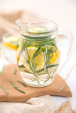 Lemon Cucumber and Rosemary Detox Water. On wooden table Royalty Free Stock Photo