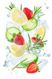 Lemon, cucumber, strawberry and rosemary flying with ices and wa royalty free stock images