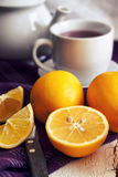 Lemon with cup of tea. Lemon on purple tablecloth with cup of tea and teapot in background Royalty Free Stock Images