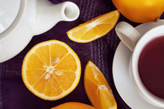 Lemon with cup of tea. Lemon on purple tablecloth with cup of tea and teapot. Top view Royalty Free Stock Photos