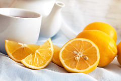 Lemon with cup of tea. And teapot in background Royalty Free Stock Image