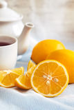 Lemon with cup of tea. And teapot in background. Copy space Stock Photo