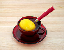 Lemon in cup with water and spoon Stock Image