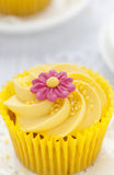 Lemon cupcake with butter cream swirl and fondant flower decoration Stock Images