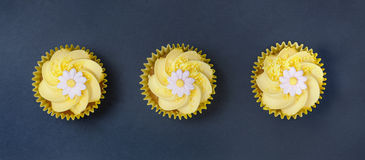 Lemon cupcakes with butter cream swirl and fondant flower decoration. Aerial view of three lemon cupcakes with fondant flower in single file on a blue slate Royalty Free Stock Photo