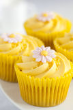 Lemon cupcakes with butter cream swirl and fondant flower decoration. Close up of Lemon cupcakes with butter cream swirl and fondant flower decorations Royalty Free Stock Images