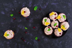 Lemon cupcakes with cherry cream. Cranberry, mint leaves. Food on a dark background. Top view Royalty Free Stock Image