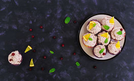 Lemon cupcakes with cherry cream. Cranberry, mint leaves. Food on a dark background. Top view Stock Photo