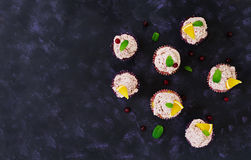 Lemon cupcakes with cherry cream. Cranberry, mint leaves. Food on a dark background. Top view Stock Image