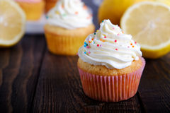 Lemon cupcakes with colorful frosting and decoration. Cupcakes with different frosting on a plate on wooden table Royalty Free Stock Photo
