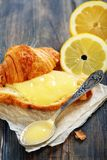 Lemon curd and teaspoon on a slice of fresh croissant. Stock Photos
