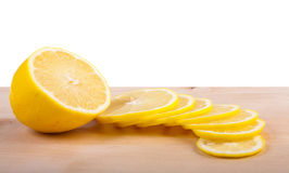 The lemon cut by segments lies on chopping board. Royalty Free Stock Images