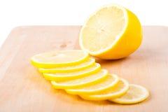 The lemon cut by segments lies on chopping board. Royalty Free Stock Photos