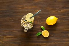 Lemon detox-cocktail in a glass jar on wooden background. Concept of healthy drinks, copy space. Lemon detox-cocktail in a glass jar on wooden background with stock image