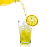 Lemon drink pouring into glass on white Stock Images