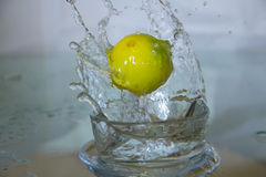Lemon drop in water. Royalty Free Stock Photography