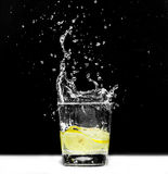 Lemon dropped into a glass Stock Photos