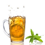 Lemon dropped into tea cup with splash and mint Royalty Free Stock Image