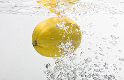Lemon dropped into water. Bubbles forming in blue water after lemon is dropped into it Stock Photography