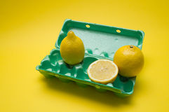 Lemon in egg carton on yellow background Royalty Free Stock Photography