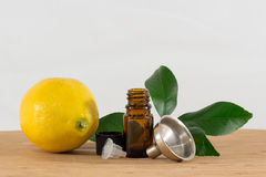 Lemon Essential Oil Bottle With Black Cap, Citrus Leaves and Funnel Royalty Free Stock Image