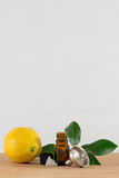 Lemon Essential Oil Bottle With Black Cap, Citrus Leaves and Funnel Royalty Free Stock Images
