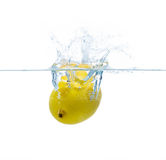 Lemon falling or dipping in water with splash Royalty Free Stock Photography