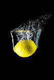 Lemon falling into the water close-up, macro, splash, bubbles, isolated Stock Images