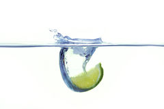 Lemon falling into water with a splash. Green lemon falling into water with a splash royalty free stock image
